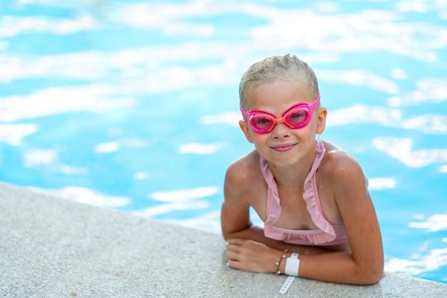 Portret uśmiechnięta dziewczyna w basenie dziecko w pływackich okularach i nadmuchiwanych rękawach latem