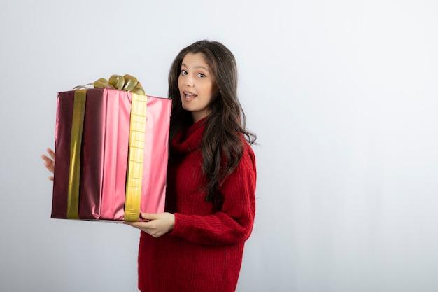 Portret uśmiechnięta dziewczyna w swetrze, trzymając pudełko.