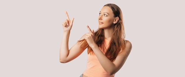 Portret uśmiechnięta dziewczyna wskazując palcem w bok na na białym tle odizolowane. pozytywna kobieta wskazuje pomysł, miejsce na reklamę