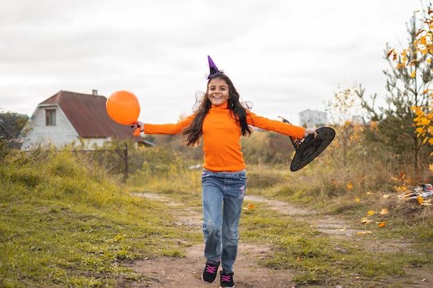 Portret uśmiechnięta dziewczyna z brązowymi włosami bieganie i skakanie. śmieszne dzieci w strojach karnawałowych na świeżym powietrzu.