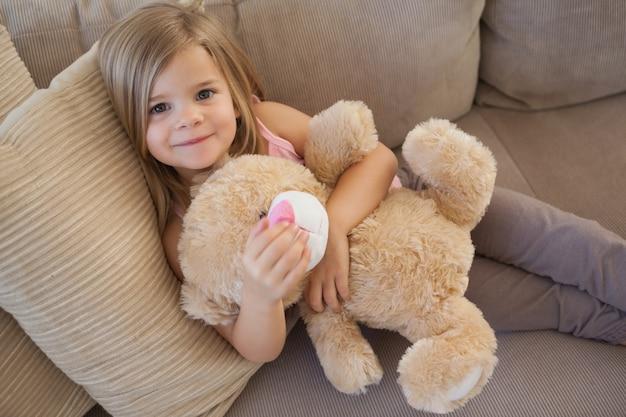 Portret Uśmiechnięta Dziewczyna Z Faszerującym Zabawkarskim Obsiadaniem Na Kanapie Premium Zdjęcia