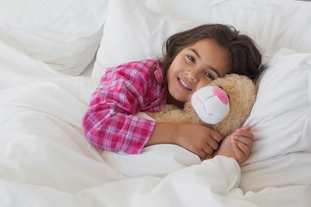 Portret uśmiechnięta dziewczyna z faszeruję zabawkarski odpoczywać w łóżku
