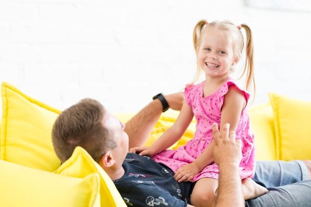 Portret uśmiechnięta dziewczyna z jej ojcem na kanapie