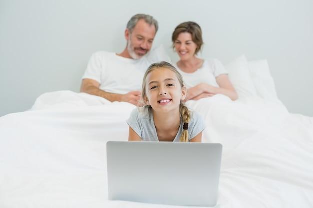 Portret uśmiechnięta dziewczyna za pomocą laptopa, podczas gdy rodzice odpoczywają w tle