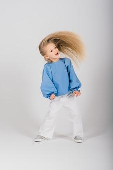 Portret uśmiechnięta dziewczynka dziecko z latającymi blond włosami, studio