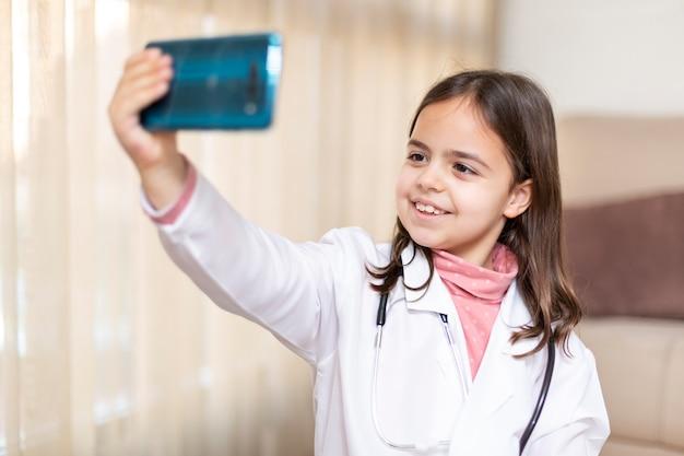 Portret uśmiechnięta dziewczynka ubrana jak lekarz robi zdjęcie telefonem komórkowym