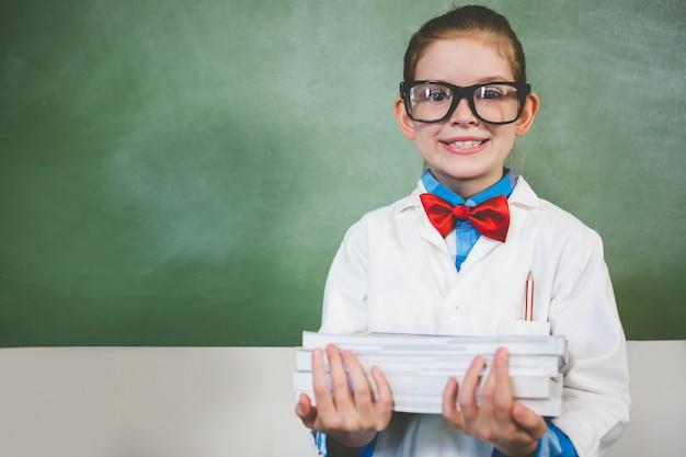 Portret uśmiechnięta dziewczyny pozycja z stertą książki w sala lekcyjnej