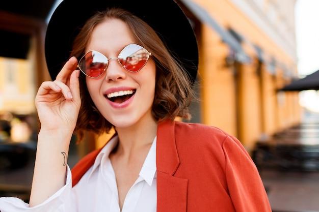 Portret uśmiechnięta europejska dziewczyna w słodkie pomarańczowe okulary przeciwsłoneczne, kurtka i czarny kapelusz. jesienna moda. kawiarnia uliczna.