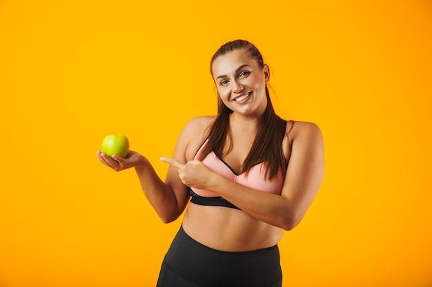 Portret uśmiechnięta gruba kobieta w stanik sportowy gospodarstwa jabłko, odizolowane na żółtym tle