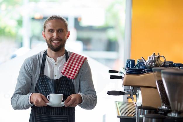 Portret uśmiechnięta kelner pozycja z filiżanką kawy