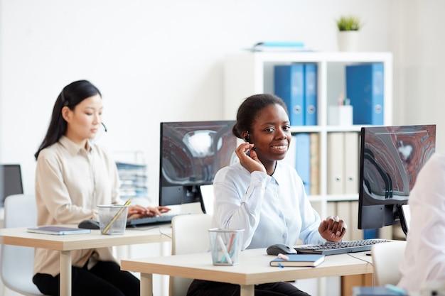 Portret uśmiechnięta kobieta african-american noszenie zestawu słuchawkowego i rozmawia z klientem podczas pracy w centrum obsługi telefonicznej
