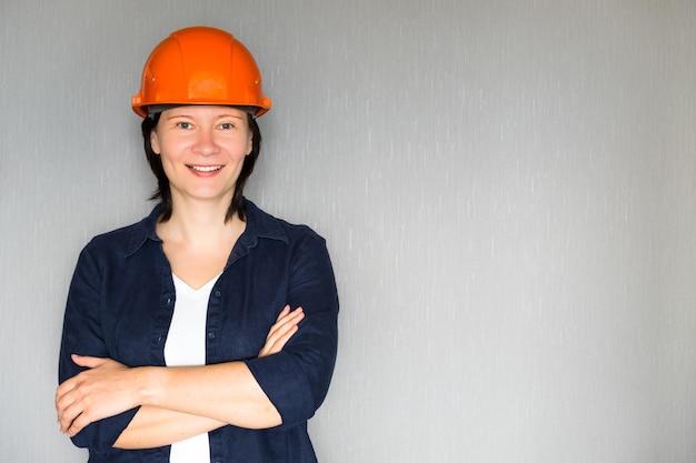 Portret uśmiechnięta kobieta architekta przeciwko szarości