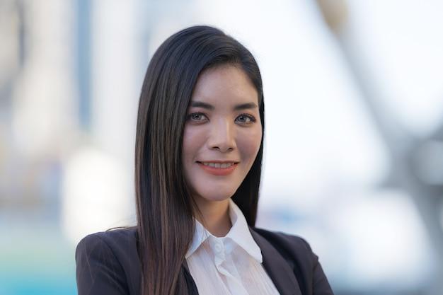 Portret uśmiechnięta kobieta biznesu, stojąc przed nowoczesnymi budynkami biurowymi