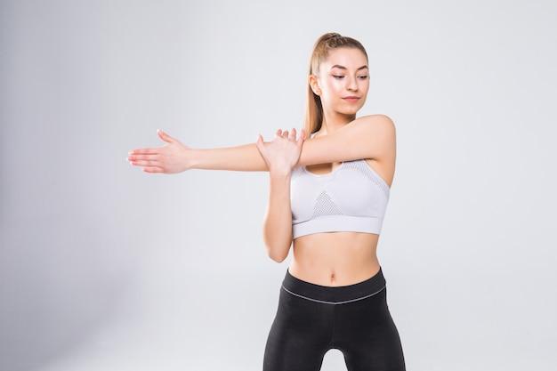 Portret uśmiechnięta kobieta fitness, rozciągając ręce na białym tle