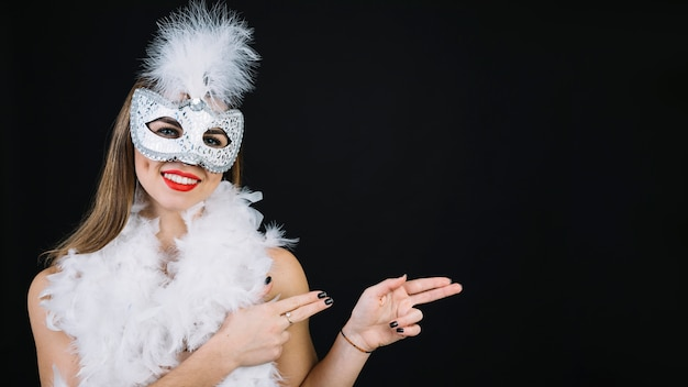 Portret uśmiechnięta kobieta jest ubranym karnawał maskową gestykulować na białym tle