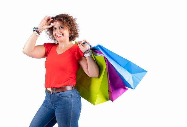 Portret uśmiechnięta kobieta jest ubranym szkła trzyma torba na zakupy i patrzeje