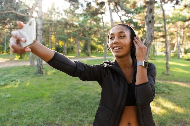 Portret uśmiechnięta kobieta lat dwudziestych ubrana w czarny dres i słuchawki, robienie zdjęcia selfie na telefonie komórkowym podczas spaceru po zielonym parku