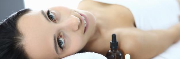 Portret uśmiechnięta kobieta na stole do masażu w centrum spa. koncepcja usług i usług hotelarskich