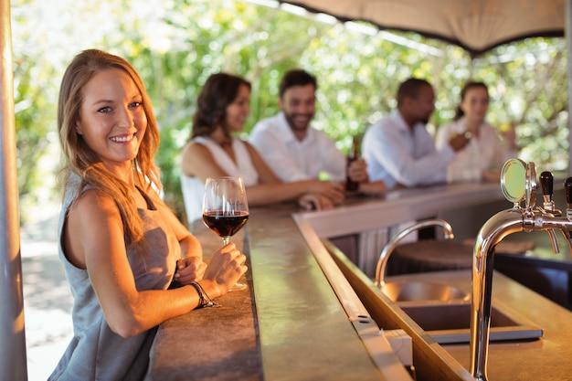 Portret uśmiechnięta kobieta o lampce czerwonego wina przy ladzie