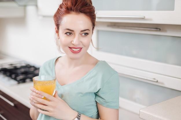 Portret uśmiechnięta kobieta pije sok pomarańczowego