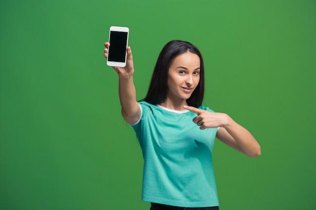 Portret uśmiechnięta kobieta pokazując pusty ekran smartfona na białym tle na zielono