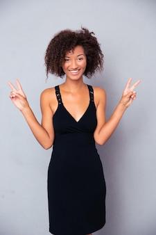 Portret uśmiechnięta kobieta pokazująca zwycięstwo palcami na szarej ścianie i patrząc z przodu