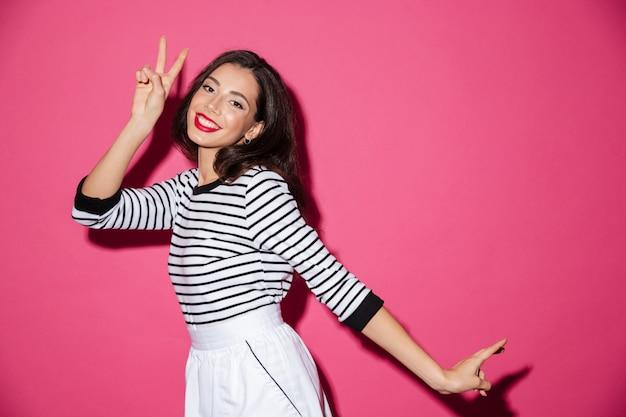 Portret uśmiechnięta kobieta pokazuje pokoju gest