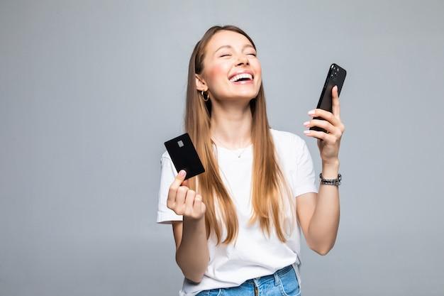 Portret uśmiechnięta kobieta posiadająca kartę kredytową i telefon komórkowy