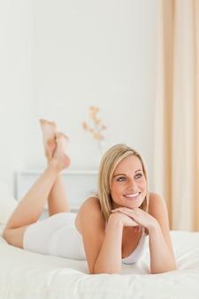 Portret uśmiechnięta kobieta pozuje na jej łóżku