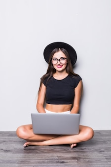 Portret uśmiechnięta kobieta siedzi na podłodze z laptopa na białym tle na szarym tle