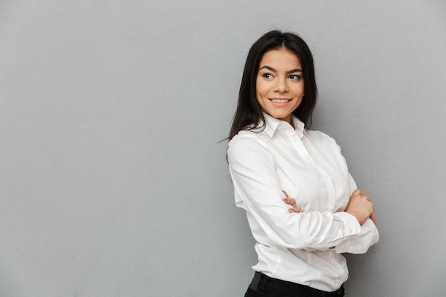 Portret uśmiechnięta kobieta sukcesu z długimi brązowymi włosami na sobie odzież biurową, patrząc na bok i stojąc z rękami skrzyżowanymi, na białym tle na szarym tle