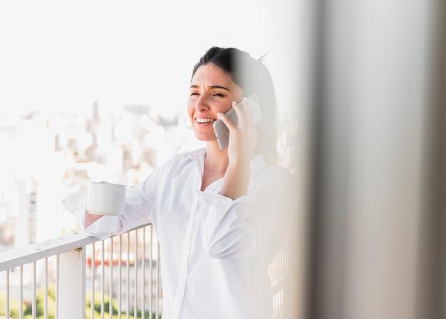 Portret uśmiechnięta kobieta trzyma filiżankę opowiada na telefonie komórkowym