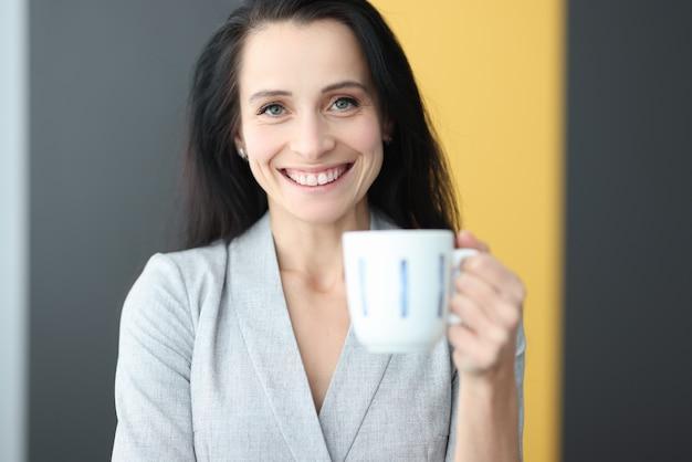 Portret uśmiechnięta kobieta trzyma kubek w dłoni. pomyślna koncepcja układu biznesowego