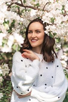 Portret uśmiechnięta kobieta w białym swetrze w pobliżu kwitnącej jabłoni, zbliżenie