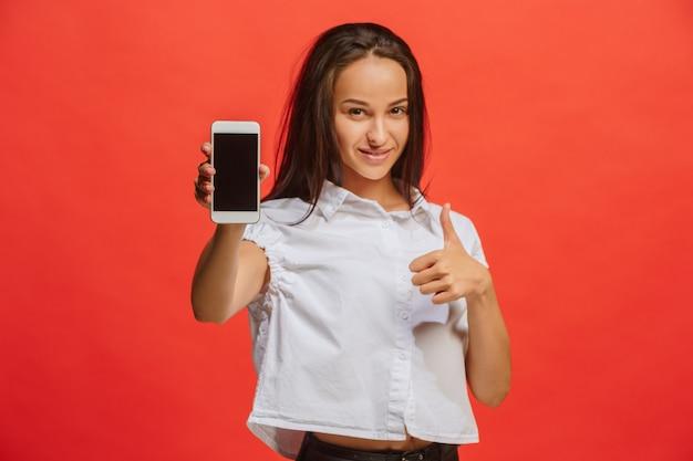 Portret uśmiechnięta kobieta w czerwieni sukni pokazuje pustego smartphone ekran