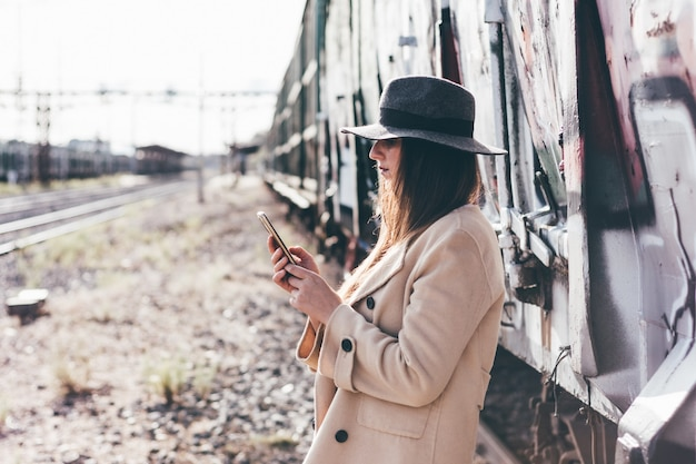 Portret uśmiechnięta kobieta w kapeluszu i beżowej kurtce za pomocą swojego telefonu na opuszczonej stacji kolejowej.