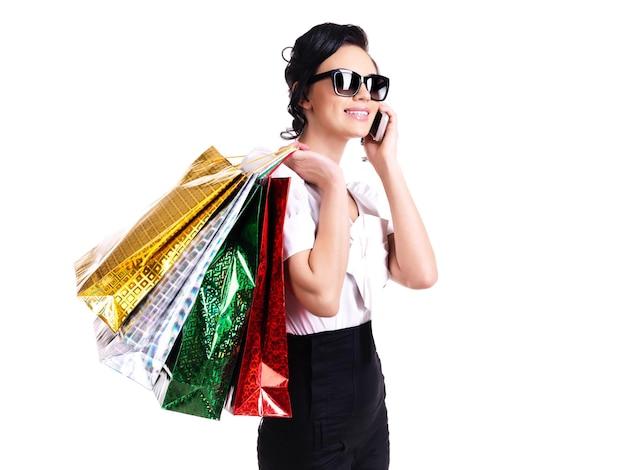 Portret uśmiechnięta kobieta w okularach z torby na zakupy rozmawia przez telefon komórkowy - na białym tle.