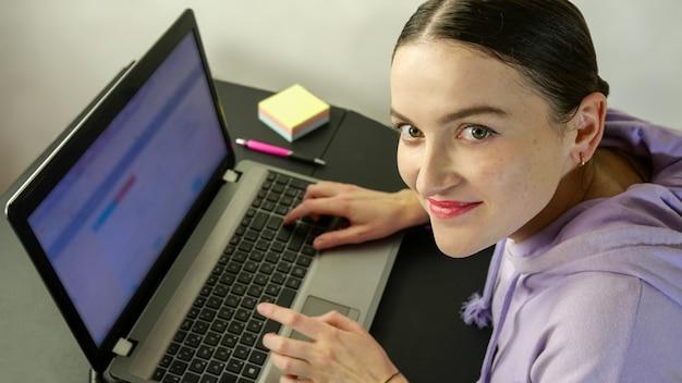 Portret uśmiechnięta kobieta w zwykłej odzieży pracy na laptopie w domowym biurze w domu.