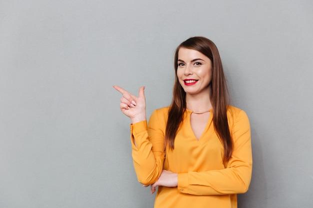 Portret uśmiechnięta kobieta wskazuje palec daleko od