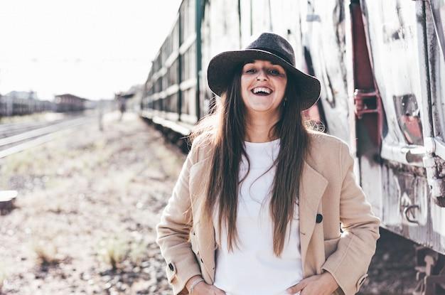 Portret uśmiechnięta kobieta z kapeluszem i beżową kurtką w opuszczonej stacji kolejowej.