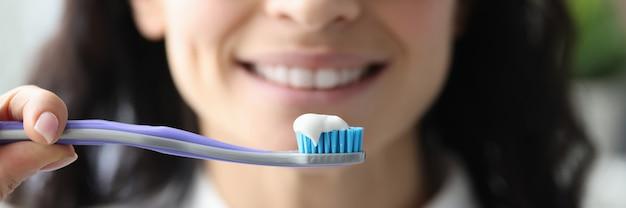 Portret uśmiechnięta kobieta z pastą do zębów i szczoteczką. koncepcja śnieżnobiały uśmiech