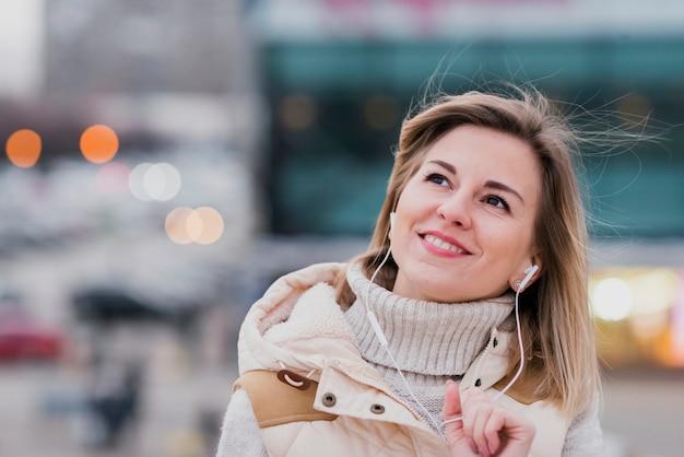 Portret uśmiechnięta kobieta z słuchawkami na dachu