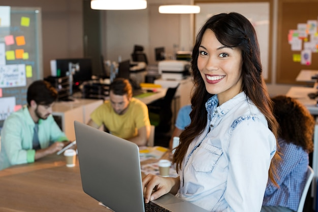 Portret uśmiechnięta kobieta za pomocą laptopa w biurze