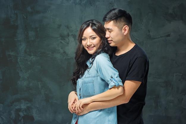Portret uśmiechnięta koreańska para na szarym studio