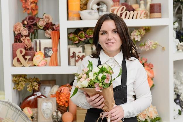 Portret uśmiechnięta kwiaciarnia stojąca obok stołu, zawijająca kwiaty w sklepie