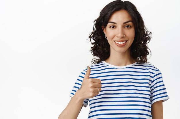 Portret uśmiechnięta ładna dziewczyna pokazuje aprobaty. kobieta z kolczykiem w nosie i kręconymi ciemnymi włosami zadowolona z jakości, poleca towarzystwo, wygląda na zadowoloną na białym tle