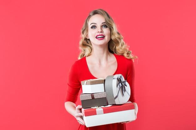 Portret uśmiechnięta ładna dziewczyna trzyma stos pudełek na prezent samodzielnie na czerwonym tle. ekspresyjne wyrazy twarzy.