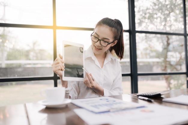Portret uśmiechnięta ładna młoda biznesowa kobieta siedzi na miejscu pracy w szkłach