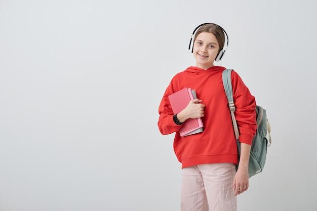 Portret uśmiechnięta ładna nastolatka w słuchawkach na sobie tornister i trzymając podręczniki szkolne