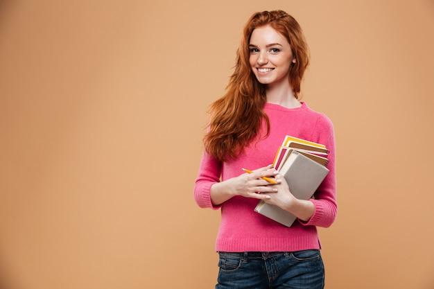 Portret uśmiechnięta ładna rudzielec dziewczyna trzyma książki